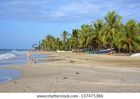 Caribbean beach with few tourists and fishing boats under coconut trees, Manzanillo, Costa Rica, Central America