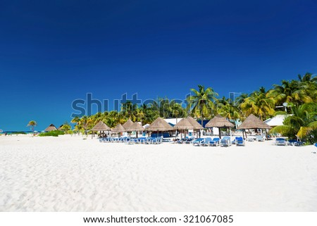 Shutterstock Caribbean beach with sun umbrellas and beds, Cancun, Mexico