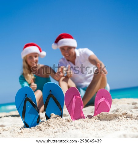 Caribbean Christmas vacation. Two pair of flip flops standing in a sand on background with  happy couple in Santa  hats, sitting on beach, smiling and showing thumbs up. Focus on sandals