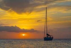 Caribbean, Grenada, Mayreau Island. Sailboat at anchor at sunset.