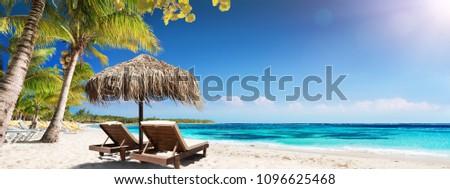 Caribbean Palm Beach With Wooden Chairs And Straw Umbrella - Idyllic Island #1096625468