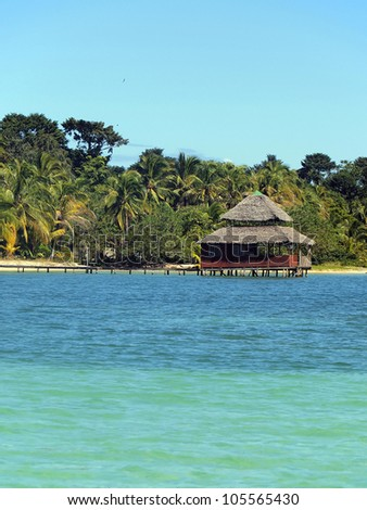 Caribbean restaurant on stilts with thatch roof over the sea and a tropical beach with lush vegetation in background