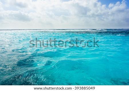 Caribbean sea bottom with blue water wave background, Cuba. Close-up blue sea. Transparent sea water. Cuba sea. Calm sea. Sunny day sea background. Endless sea. Daylight sea. Sea water. Turquoise sea.