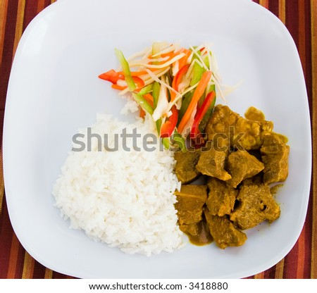 Caribbean style curried goat served with steamed rice. Dish accompanied with vegetable salad. Shallow DOF.
