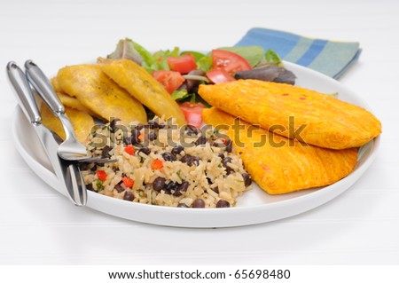 Caribbean style meal with gallo pinto, meat patties and fried plantain.