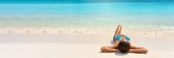 Caribbean suntan woman lying on white sand beach tanning relaxing under the sun in blue bikini. Banner panorama of turquoise ocean background travel tourist.