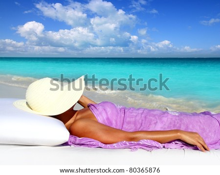 Caribbean tourist resting in tropical beach with hat lying on resort bed