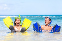 Caribbean vacation beach fun couple on summer holiday swimming with snorkel mask, ocean watersport activity.