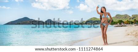 Caribbean vacation beach selfie woman panorama. Asian bikini girl taking self-portrait pictures on Jolly beach, Antigua and Barbuda, cruise travel destination. Banner crop.