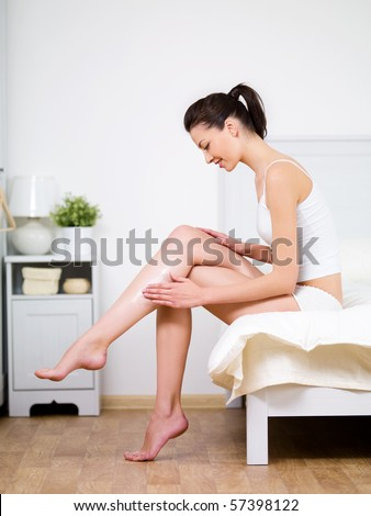 Caring about woman's leg with moisturizing cream by young beautiful woman sitting on a bed at home