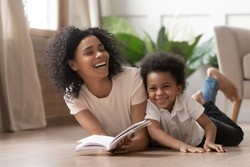 Caring african american mother baby sitter tell funny fairy tale story to smart cute kid son laugh lay on warm floor together, loving mixed race mom read book having fun with little child boy at home