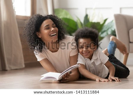 Caring african american mother baby sitter tell funny fairy tale story to smart cute kid son laugh lay on warm floor together, loving mixed race mom read book having fun with little child boy at home Foto stock ©