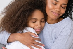 Caring african american single mother hugging teenage daughter, happy black mom embracing teen girl cuddling enjoy moment of love, mum and child warm relationship, motherhood concept, close up view