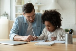 Caring Caucasian father help biracial little daughter with homework at home, loving European dad and small African American girl child study together in kitchen on quarantine, homeschooling concept