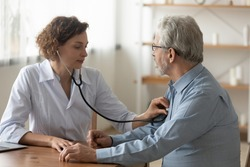 Caring Caucasian female doctor use phonendoscope examine mature male patient heart rate at consultation in hospital. Woman nurse or GP use stethoscope listen to senior man heartbeat in clinic.