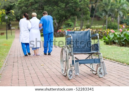 caring doctor and nurse helping senior patient get up from wheelchair and walk