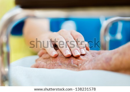 Caring doctor or nurse holding elderly lady's hands in wheelchair