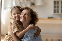 Caring embraces of love. Happy foster mother and little adopted kid daughter hug tight touch cheeks share tenderness devotion. Smiling girl cuddle with beloved grown elder sister at home. Copy space