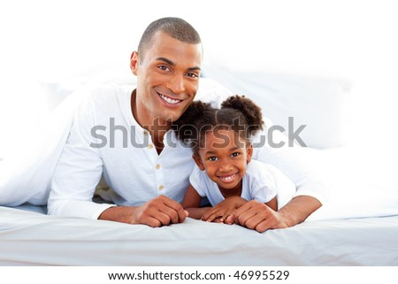 Caring father and his daughter lying on a bed smiling at the camera - stock photo