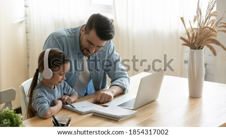 Caring father helping little daughter with school homework, sitting at table at home, child schoolgirl wearing headphones studying online, using laptop, dad checking tasks, homeschooling concept