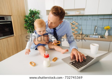 Caring father. Nice handsome adult man holding his baby daughter and looking at her while pressing the button on the laptop #732745369