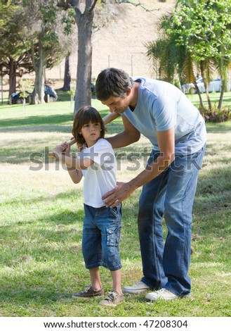 Caring father teaching baseball to his son in the park