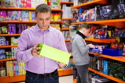 Caring father visiting toy store in search of new playthings for his child, looking narrowly at carton box
