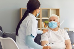 Caring female doctor supporting and cheering up senior male patient during home visit. Therapeutist and aged white-haired man, both wearing medical face masks, communicating and discussing treatment