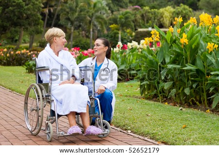 caring female nurse talking to disabled senior patient outdoors