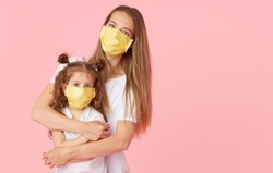Caring for loved ones. Young mother hugs little daughter in protective medical masks during Covid-19 pandemics. Studio pink background