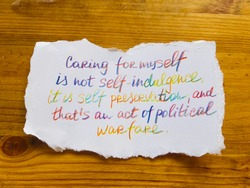 Caring for myself is not self indulgence. It's self preservation, and that's an act of political warfare. Handwritten text. wooden table as background.