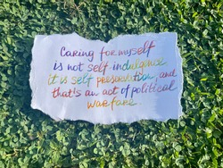 Caring for yourself is not self indulgence that's an act of political warfare! Handwritten message. Green grass as background.