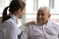 Caring geriatric nurse in white coat cares for grey-haired elderly man in nursing home, listen him relieve solitude, provide support help during visit at home. Homecare eldercare caregiving concept
