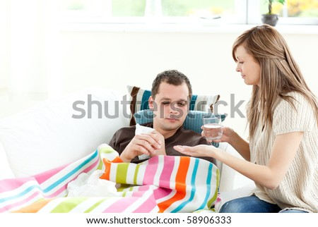 Caring girlfriend giving his sick boyfriend pills in the living room
