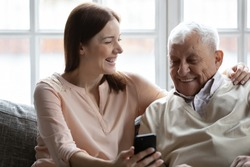 Caring grown up granddaughter and grandfather sit on couch holding cellphone. Young generation teach old how make videocall, to web surfing. Caretaker help to 80s man with virtual app services concept