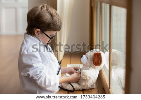 Caring little boy kid in whites and glasses listen to plush toy heartbeat with stethoscope, cute small child play act as doctor cure examine teddy bear heart in hospital, healthcare, medicine concept Foto stock ©