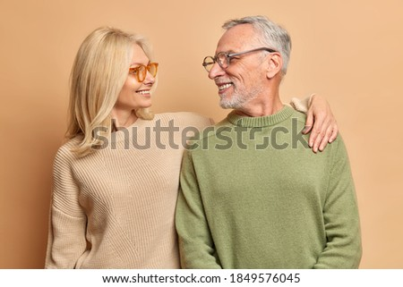 Caring middle aged woman embraces her husband looks with love and broad smile. Married mature couple have good relationships isolated on brown background. Smiling aged husband and wife pose for photo