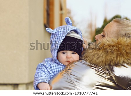 Caring mom holding her baby boy and adjusting his cap on back view. Happy family, mother and son, solicitude, carefulness and wintertime concept. Сток-фото ©