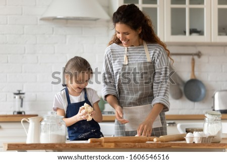 Caring mother and small adorable daughter cooking together in kitchen, mom teaches cute kid girl kneading dough for domestic pie preparing surprise for family, enjoy process and communication concept