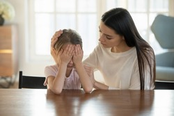Caring mother calming and hugging crying upset little daughter, sitting at desk together, loving mum expressing support, comforting offended preschool girl, children psychologist concept