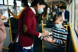 Caring mother disinfecting son's hands while commuting by bus during COVID-19 pandemic.