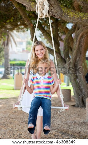 Caring mother pushing her daughter on a swing in a park - stock photo