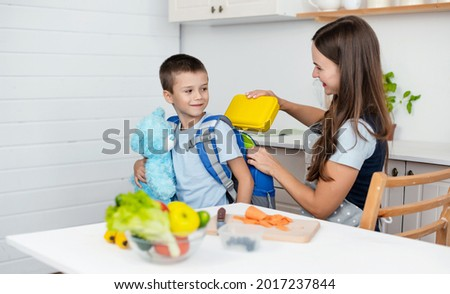 Caring mother puts yellow plastic lunch box to her son in a school backpack. School food or lunch, concept image.