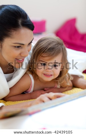 Caring mother reading a book with her girl in the bedroom
