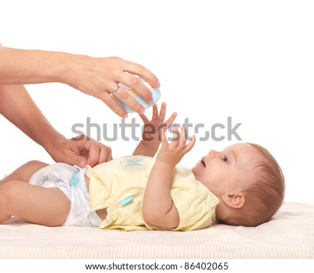 Caring mother's hands playing with little baby boy