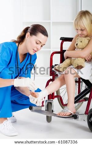 caring nurse bandage little girl\'s ankle