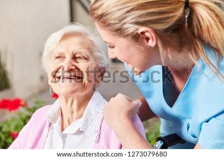 Caring Nurse Caring for Senior Woman in Wheelchair at Nursing Home