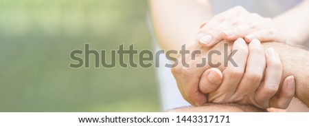 Caring nurse helping senior man sitting on bench in gaden. Asian woman, caucasian man. Holding hands, with copy space. Web banner frame.