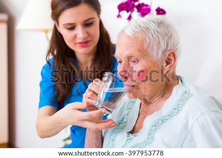 Caring nurse helping sick elderly woman to drink in bed in a nursing home.