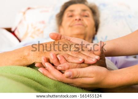 Caring nurse holding kind elderly lady\'s hands in bed.